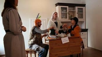 Алиса, для того чтобы попасть на работу в богадельню пришла на экзамен. За столом преподаватели: мартовский заяц (слева), в центре — Соня, медсестра, она уснула стоя, после суток, справа — шляпник